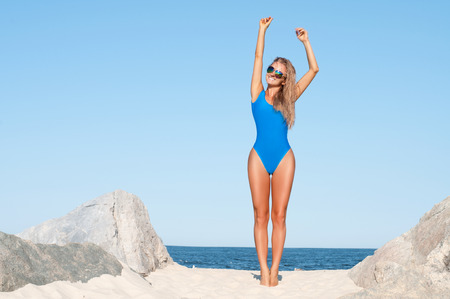 Foto de Summer lifestyle. Sexy tanned woman in blue one-piece swimsuit on the tropic beach - Imagen libre de derechos
