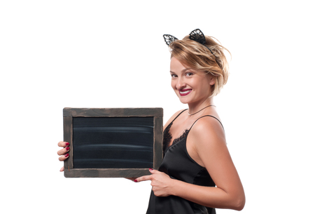 Beautiful woman with carnival cat ears holding blank chalkboard. Halloween concept