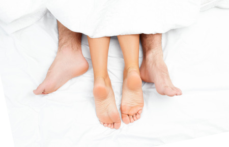Photo pour Close up of the feet of a couple on the bed. Loving couple is lying on bed under blanket  - image libre de droit