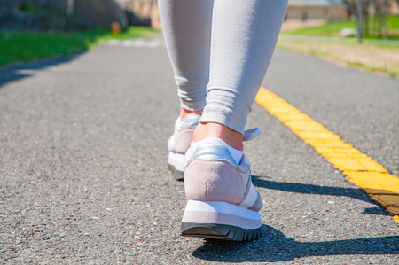Photo pour Walking. Close-up of women's running shoes on a paved trail. Female feet in sneakers. - image libre de droit