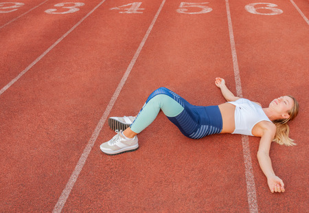 Photo for Tired woman runner taking a rest after run lying on the running track - Royalty Free Image