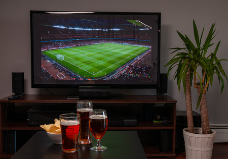 Photo pour Beer glasses and chips in front of tv, football at home, soccer supporters - image libre de droit