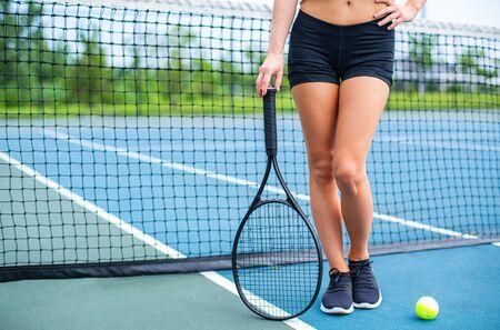 Photo pour Beautiful female legs with tennis racket on tennis blue court - image libre de droit