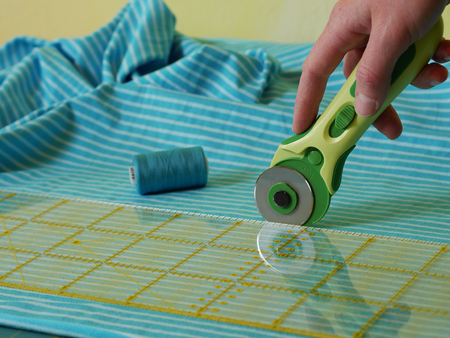 Photo for close up of cutting fabric with rotary cutter - Royalty Free Image