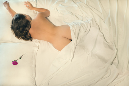 Foto de Beautiful naked female sleeping in bed. Flower on a pillow near a beautiful girl. View from above. A conceptual photo of the relationship between a man and a woman - Imagen libre de derechos