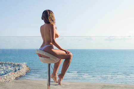 Foto de Naked woman in the headphones listening music sitting on a high chair on the balcony and looking on the sea and sky. - Imagen libre de derechos