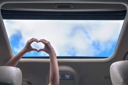 Foto per girl traveling by car and holds her hands in the form of heart out from open hatch of a vehicle. Travel lifestyle concept - Immagine Royalty Free