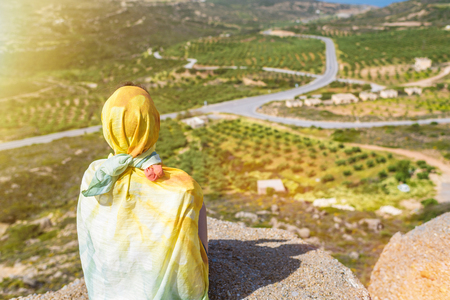 Photo pour A lonely Muslim woman  traveler in a colorful scarf sits on top of a mountain. - image libre de droit