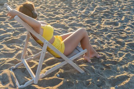 Foto de Relaxed woman sitting on a sunbed wearing headphones meditating listening to music on the beach at sunset or sunrise. Girl in the yellow summer suit, sand, looking on the sea. - Imagen libre de derechos