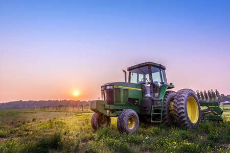 Photo pour Farm Tractor in a field on a Maryland Farm at sunset - image libre de droit