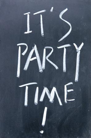 it is party time written with chalk on blackboard