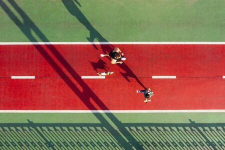 Foto de marathon runners with dog. Sport life style. Active couple on red and green bridge. Keep fit motivation. Aerial drone top view - Imagen libre de derechos