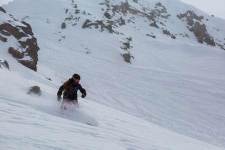 Male snowboarder snowboarding on fresh snow on ski slope on Sunny winter day in the ski resort in Georgia