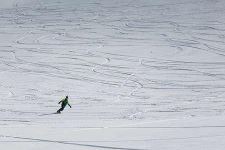 Man snowboarder snowboarding on fresh white snow on ski slope on Sunny winter day