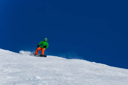 Male snowboarder snowboarding on fresh snow on ski slope on Sunny winter day in the ski resort in Georgia. Travel adventure concept. space for text