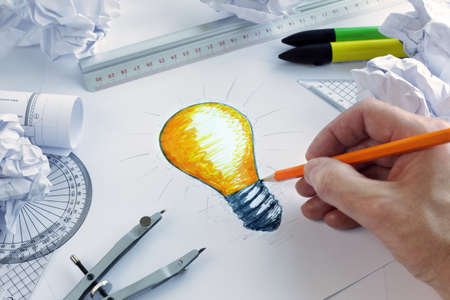Photo pour Designer drawing a light bulb, concept for brainstorming and inspiration - image libre de droit