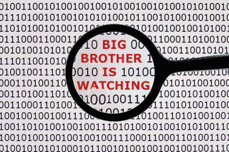 Photo pour Internet security concept the words big brother is watching on a digital tablet screen with a magnifying glass - image libre de droit