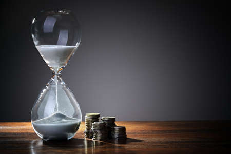 Photo pour Deadline and time is money concept with hourglass and British coin currency - image libre de droit