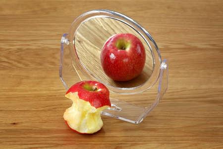 Foto de Metaphor for anorexia or bulimia eating disorder, apple in front of a mirror - Imagen libre de derechos