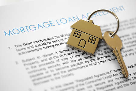 Photo pour Mortgage loan agreement application with house shaped keyring - image libre de droit