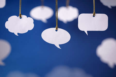 Foto de Blank white speech bubbles hanging from a cord - Imagen libre de derechos