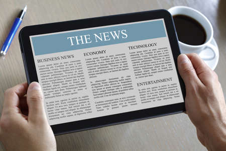 Photo pour Reading the news on a digital tablet - image libre de droit