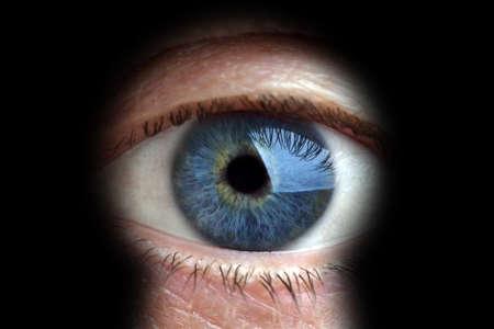 Mans eye looking through a blured keyhole