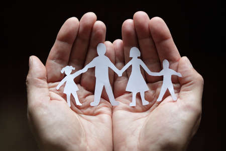 Foto de Cutout paper chain family with the protection of cupped hands - Imagen libre de derechos