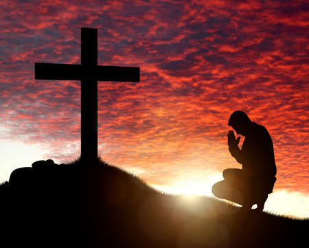 Photo pour Silhouette of man praying to a cross with heavenly cloudscape sunset concept for religion, worship, love and spirituality - image libre de droit