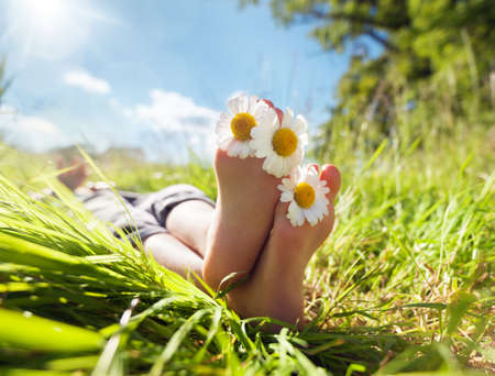 Photo for Child with daisy between toes lying in meadow relaxing in summer sunshine - Royalty Free Image