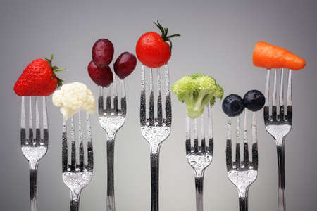 Photo pour Fruit and vegetable of silver forks against a grey background concept for healthy eating, dieting and antioxidant - image libre de droit