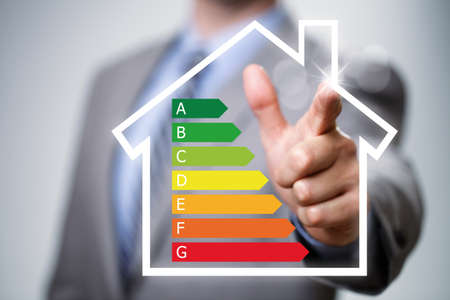 Foto de Businessman pointing to energy efficiency rating chart and house icon concept for performance, efficiency and environmental conservation - Imagen libre de derechos
