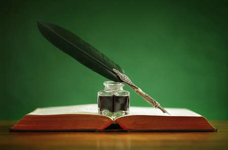 Foto de Quill pen and inkwell resting on an old book with green background concept for literature, writing, author and history - Imagen libre de derechos