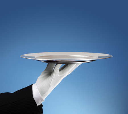 Photo pour Waiter holding an empty silver platter ready for product placement - image libre de droit