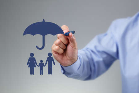 Foto de Businessman hand drawing an umbrella above a family concept for protection, security, finance and insurance - Imagen libre de derechos