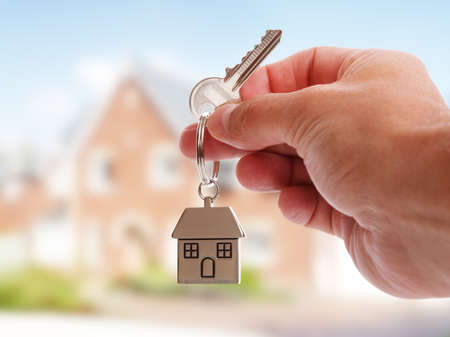 Photo pour Holding house keys on house shaped keychain in front of a new home - image libre de droit