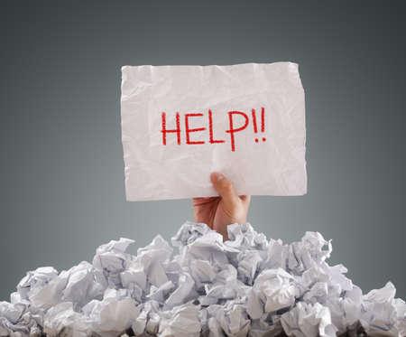 Photo pour Businessman buried under crumpled pile of papers with a help sign - image libre de droit