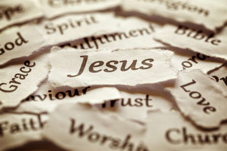 Photo pour Torn paper words of religion with focus on word Jesus - image libre de droit