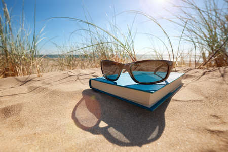 Photo pour Book and sunglasses on the beach for summer reading and relaxing - image libre de droit