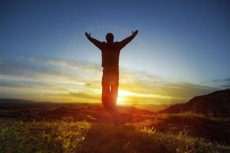 Photo pour Silhouette of a man with hands raised in the sunset concept for religion, worship, prayer and praise - image libre de droit