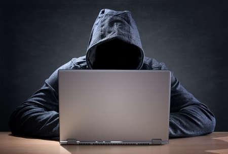 Foto de Computer hacker stealing data from a laptop concept for network security, identity theft and computer crime - Imagen libre de derechos