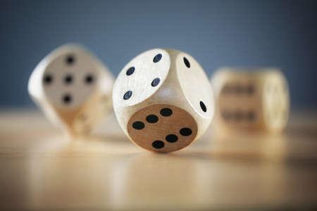 Photo pour Rolling three dice on a wooden desk - image libre de droit