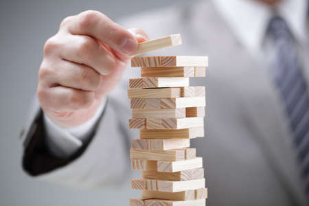 Foto de Planning, risk and strategy in business, businessman gambling placing wooden block on a tower - Imagen libre de derechos
