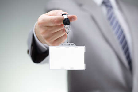 Foto de Businessman showing a blank identity name card on a lanyard - Imagen libre de derechos