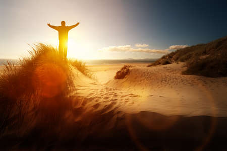 Photo pour Silhouette of a man with hands raised in the sunset on a beach concept for religion, worship, prayer and praise - image libre de droit