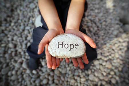 Photo pour Child on a beach with hands cupped holding stone pebble with the word hope engraved concept for faith, love, spirituality and religion - image libre de droit