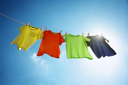 Photo pour T-shirts hanging on a clothesline in front of blue sky and sun - image libre de droit