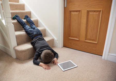 Foto de Child falling down the stairs whilst playing on digital tablet not concentrating concept for safety at home - Imagen libre de derechos