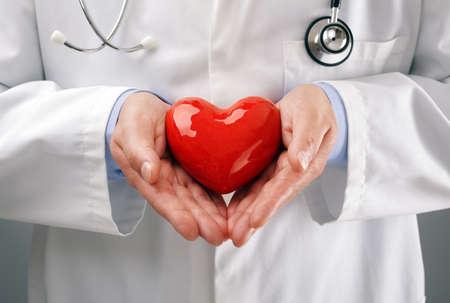 Foto de Doctor or cardiologist holding heart with care in hands concept for healthcare and diagnosis medical cardiac pulse test - Imagen libre de derechos