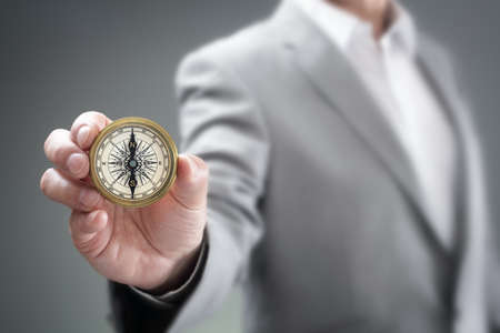 Businessman holding compass showing direction concept for guidance, strategy and business orientation